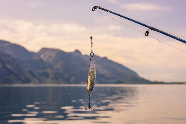 Fishing rod over lake against sky