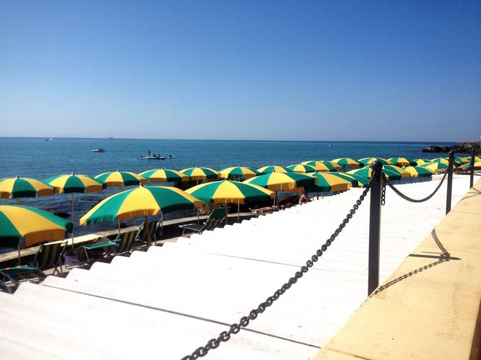 Open Parasols By Sea Against Clear Sky