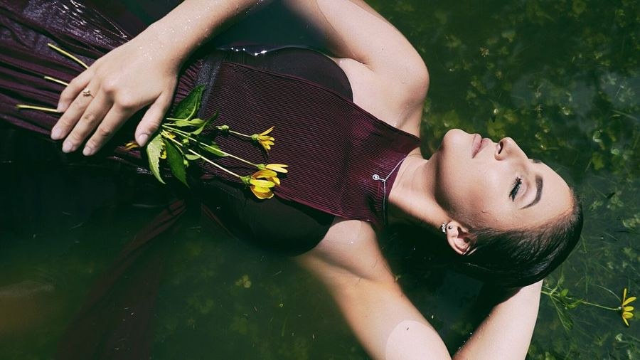 Directly Above Shot Of Young Woman With Flowers While Relaxing In Lake