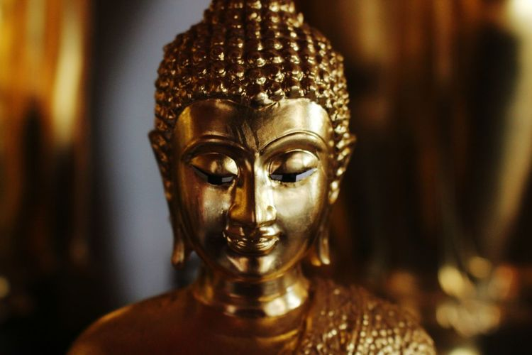 Close-up of gold buddha statue in temple