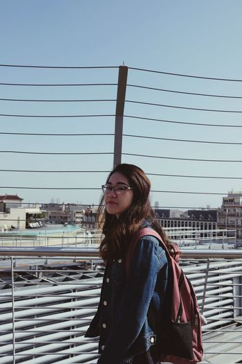 Portrait of beautiful young woman standing by railing against sky