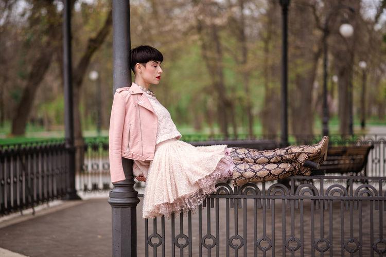 Fashionable woman sitting on railing