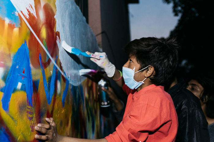 An Indian boy helps to paint a mural in Lodhi Colony, New Delhi. India Indian Indiapictures Lodhicolony Delhi Flash Flash Photography Child Boy Graffiti Artist Art And Craft Paint Painter - Artist People Street Art Workshop