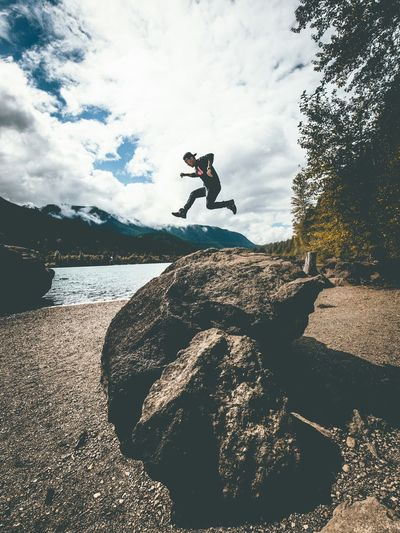Scenic View Of A Man Jumping Over A Stone