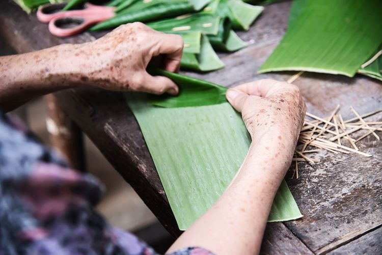 Cropped hand of woman holding banana leaf on table