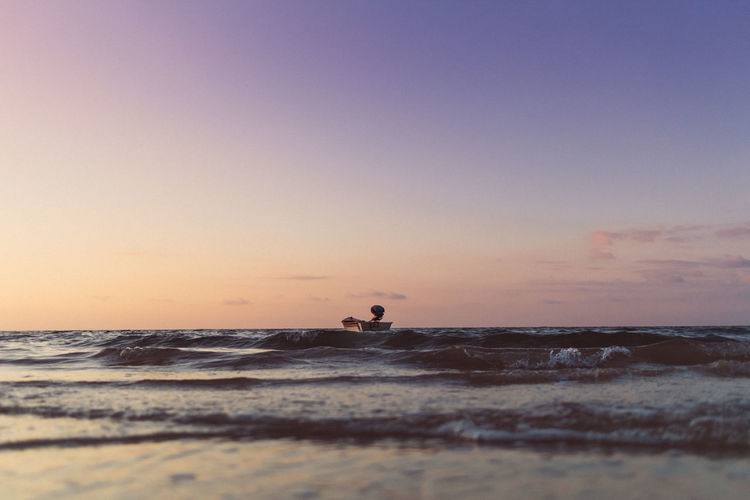 Tiny boat isolated on the sea on colorful sunset. concept of lonely.