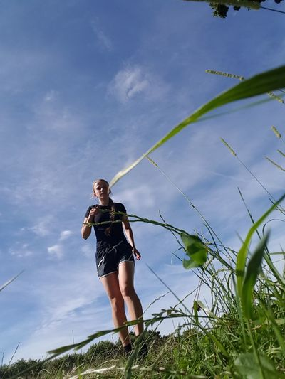 Low angle view of woman running on grassy field against blue sky