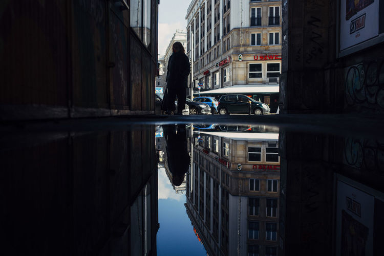 Reflection of woman on canal in city buildings