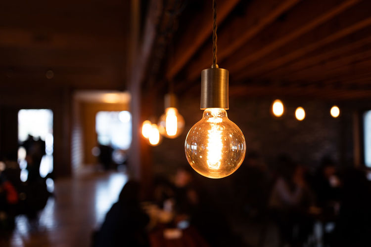 Close-up of illuminated light bulb hanging from ceiling in cafe