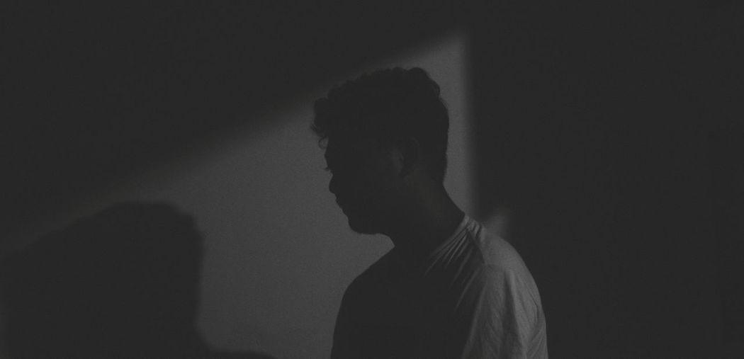 Silhouette man standing against wall in darkroom