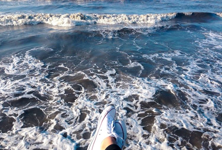 Low section of woman wearing shoes against sea