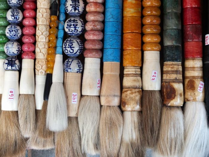 Full frame shot of various colorful brushes for sale at market