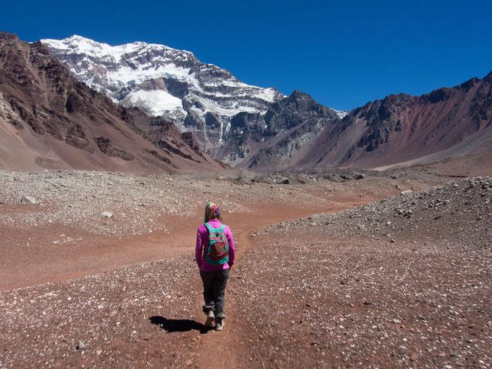 Full length rear view of man walking in desert