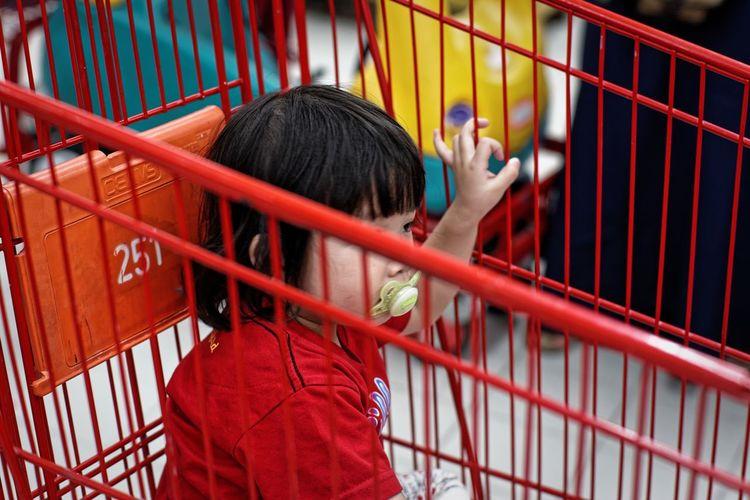 Girl sucking pacifier in crib