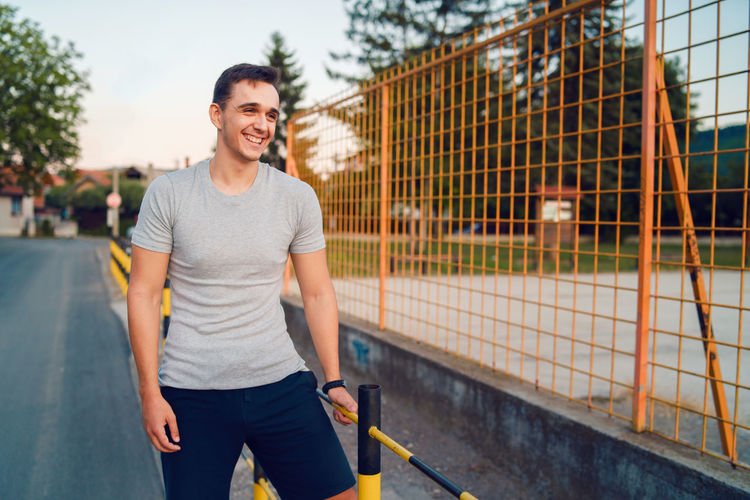 Smiling young man standing by railing on road