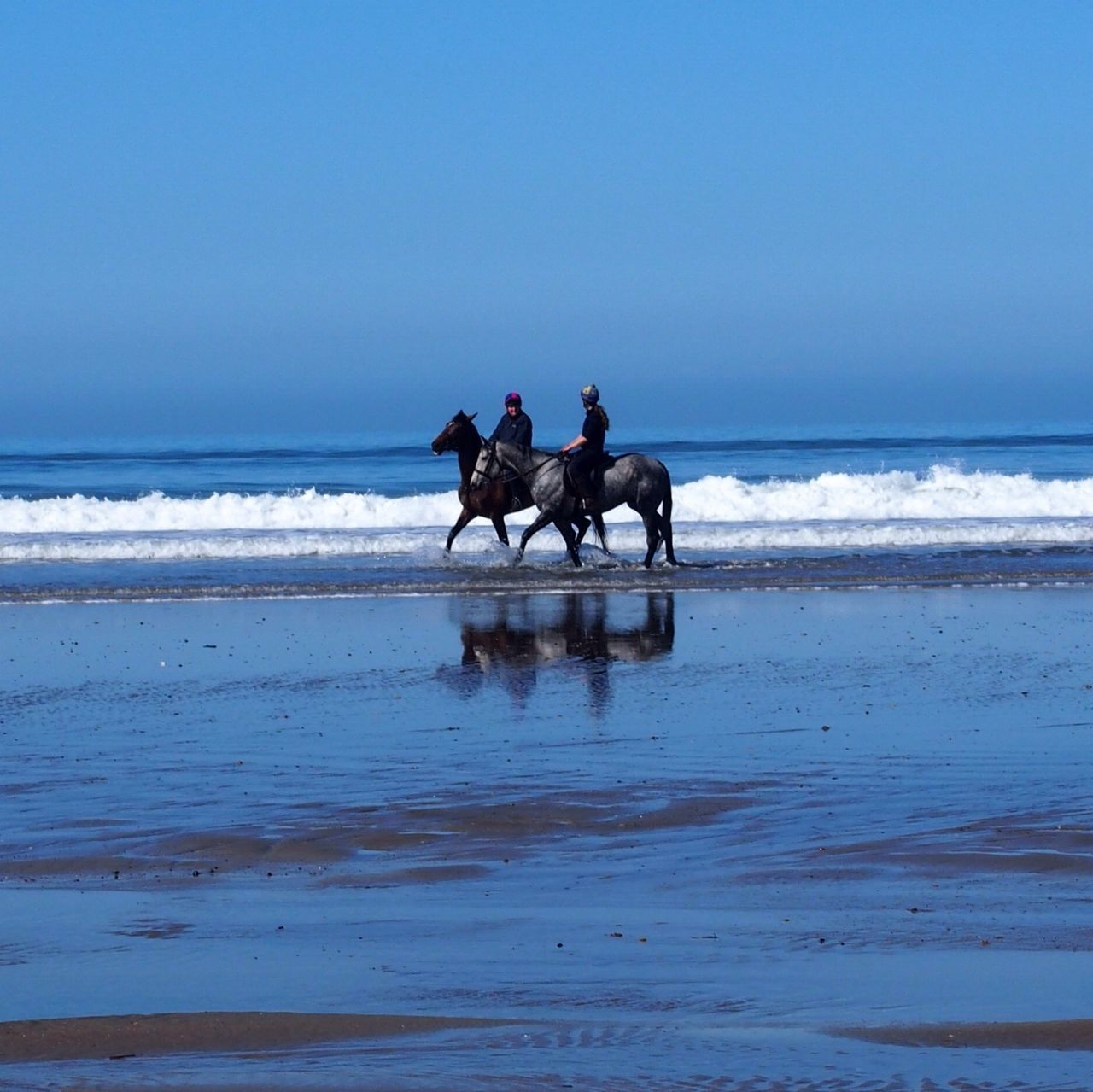 Man And Woman Riding Horses On Beach At Newgale