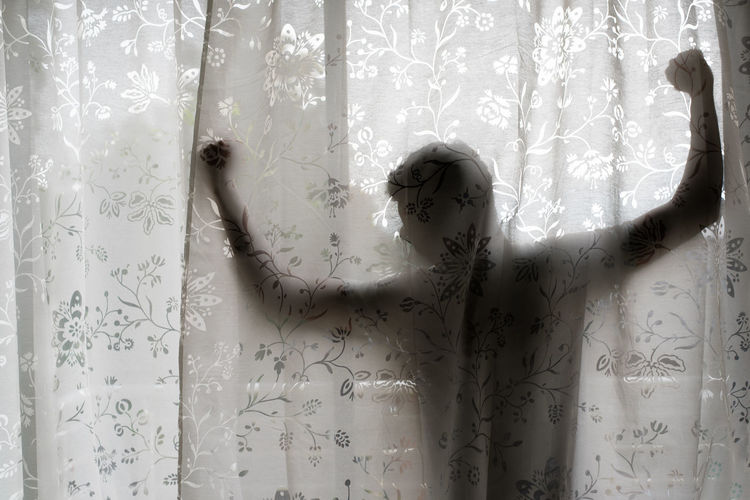 Man with arms outstretched standing in balcony seen through curtain