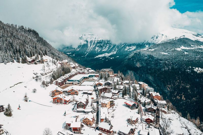High angle view of buildings on snow covered mountain against cloudy sky during winter