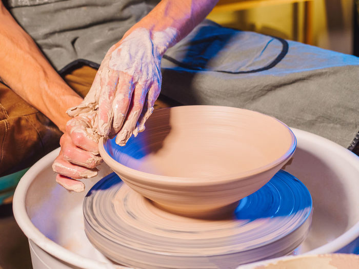 Cropped Hand Of Potter Making Pot Using Pottery Wheel In Workshop