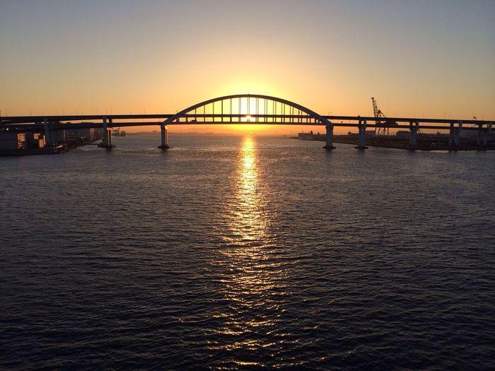 Silhouette bridge against orange sky