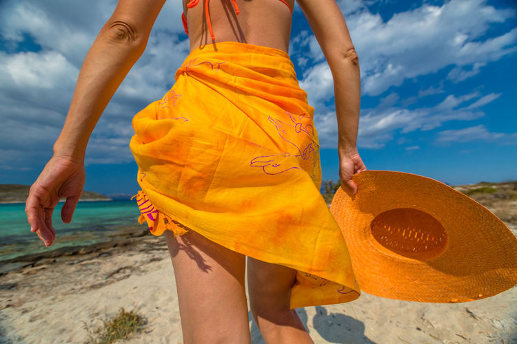 Midsection of woman in yellow dress standing at beach against sky