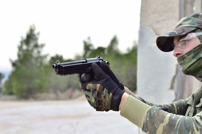 Close-Up Of Army Soldier Aiming Gun