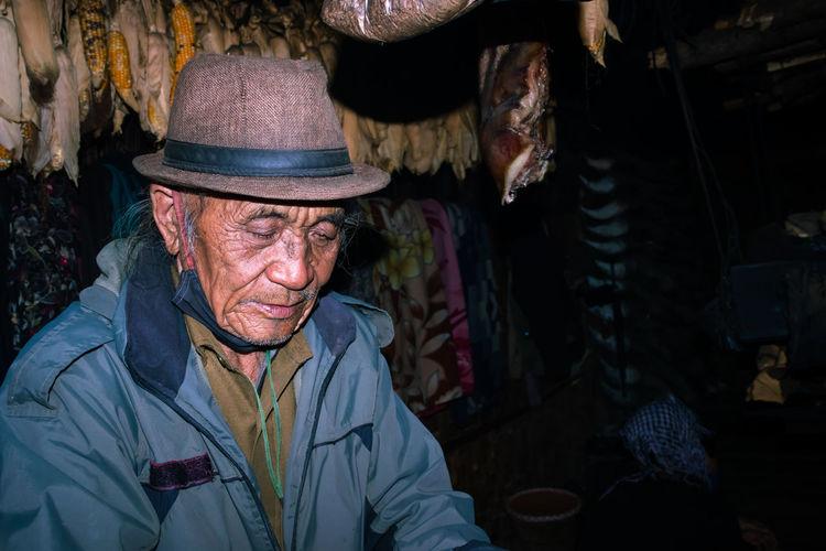 Senior man wearing hat while sitting at market stall
