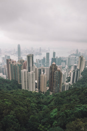 High angle view of modern buildings in city against cloudy sky