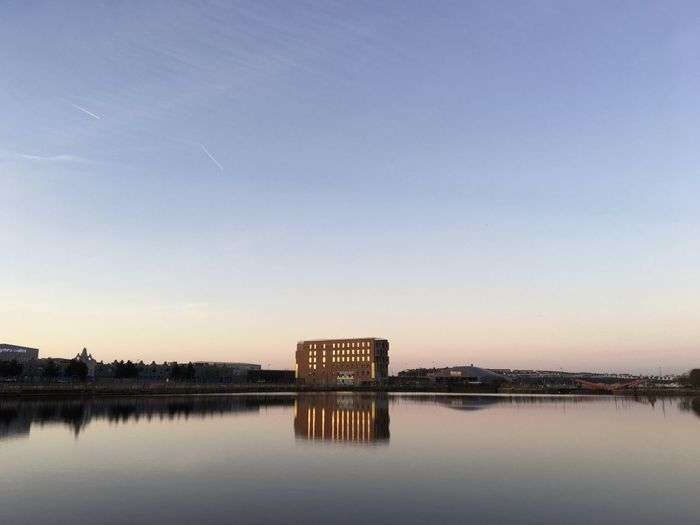 Reflection Of Building In Lake During Sunset