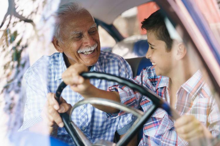 Senior man looking at grandson driving car