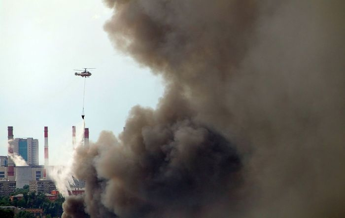 The helicopter extinguishes the fire City Helicopter Smoke Architecture Building Exterior Built Structure City Conflagration Day Fire Fighting Fire Fighting Helicopter Fire Suppression Fog No People Outdoors Sky Skyscraper Smoke - Physical Structure Water