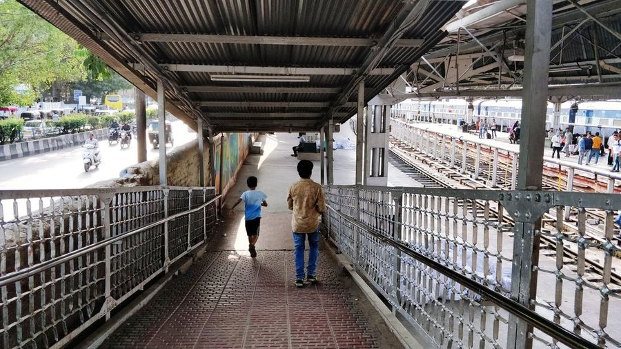 Road and Rail by the sides Railway Station Pune Station Full Length Water Men City Under Women Child Walking Footbridge