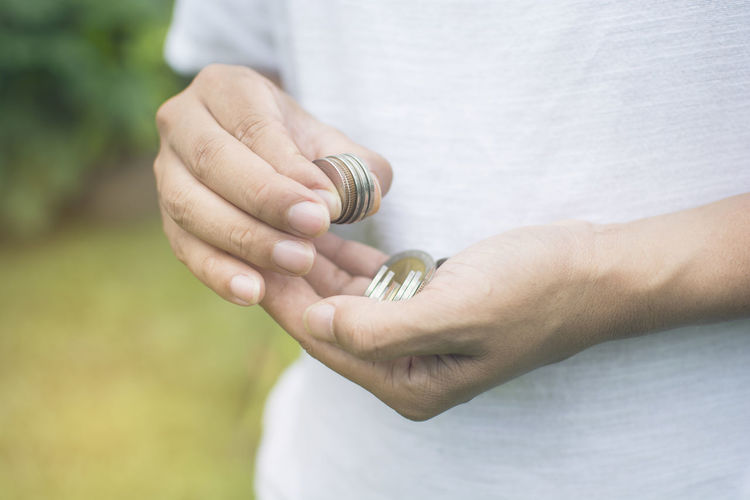 Midsection Of Man Holding Coins