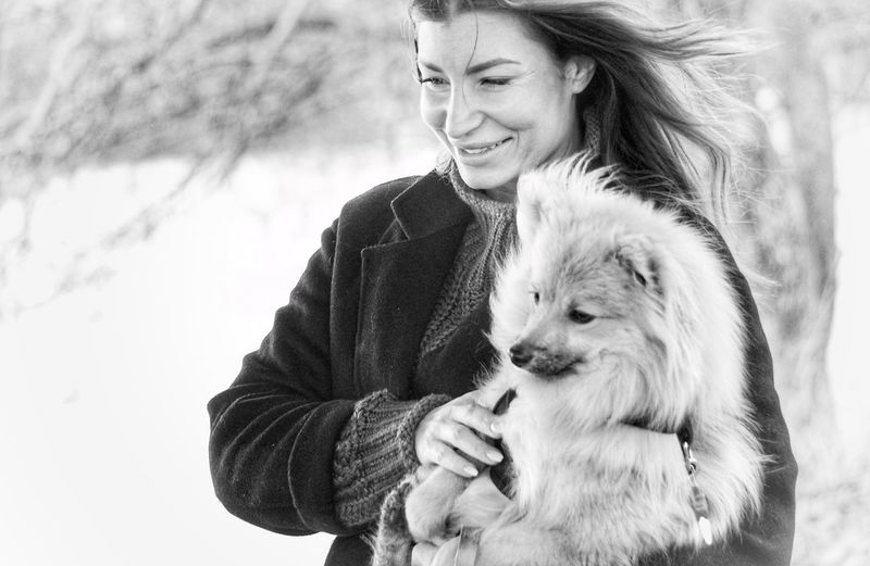 Smiling woman carrying dog while standing outdoors