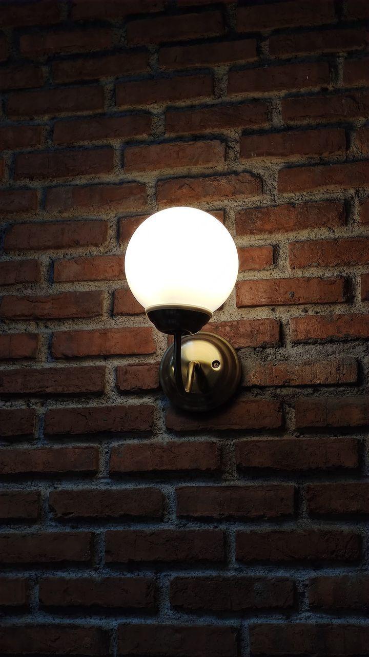 LOW ANGLE VIEW OF LIGHT BULB ON BRICK WALL