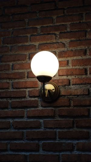 Low angle view of light bulb mounted on brick wall