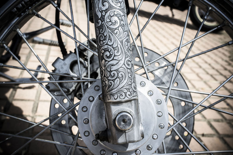 Front fork decorated with tattoo motifs of a motorbike. Closeup Art And Craft Backgrounds Bicycle Close-up Day Detail Focus On Foreground Full Frame Gear Land Vehicle Metal Mode Of Transportation No People Outdoors Pattern Silver Colored Spoke Transportation Travel Vehicle Part Wheel