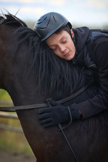 Teenage boy sleeping on horse