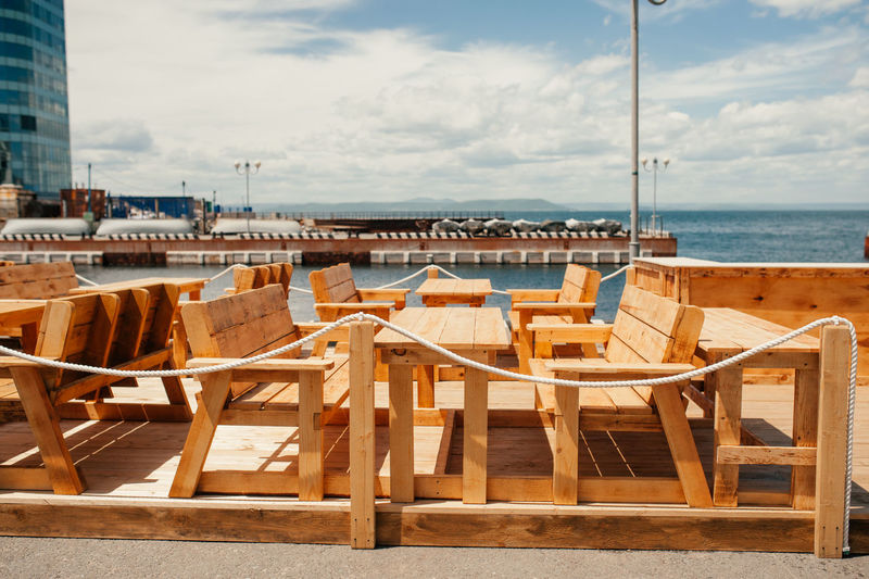 Empty chairs and tables at beach against sky
