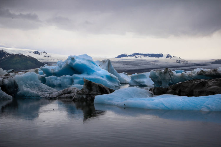 Icebergs melting in lagoon against cloudy sky