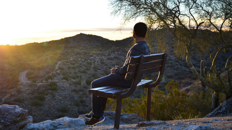 Man Sitting On Bench Against Mountains During Sunset