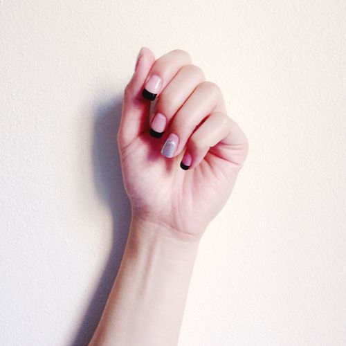 Cropped Image Of Hand With Nail Polish Against Wall