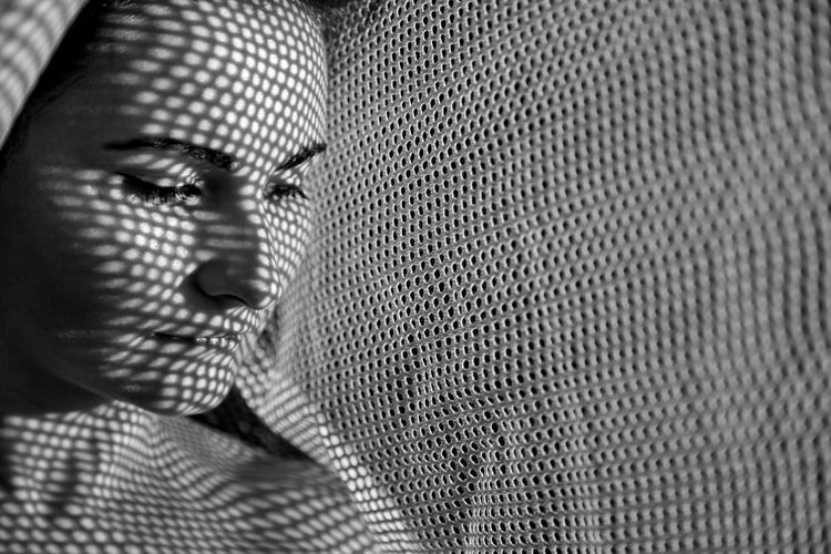 Close-up of woman by curtain