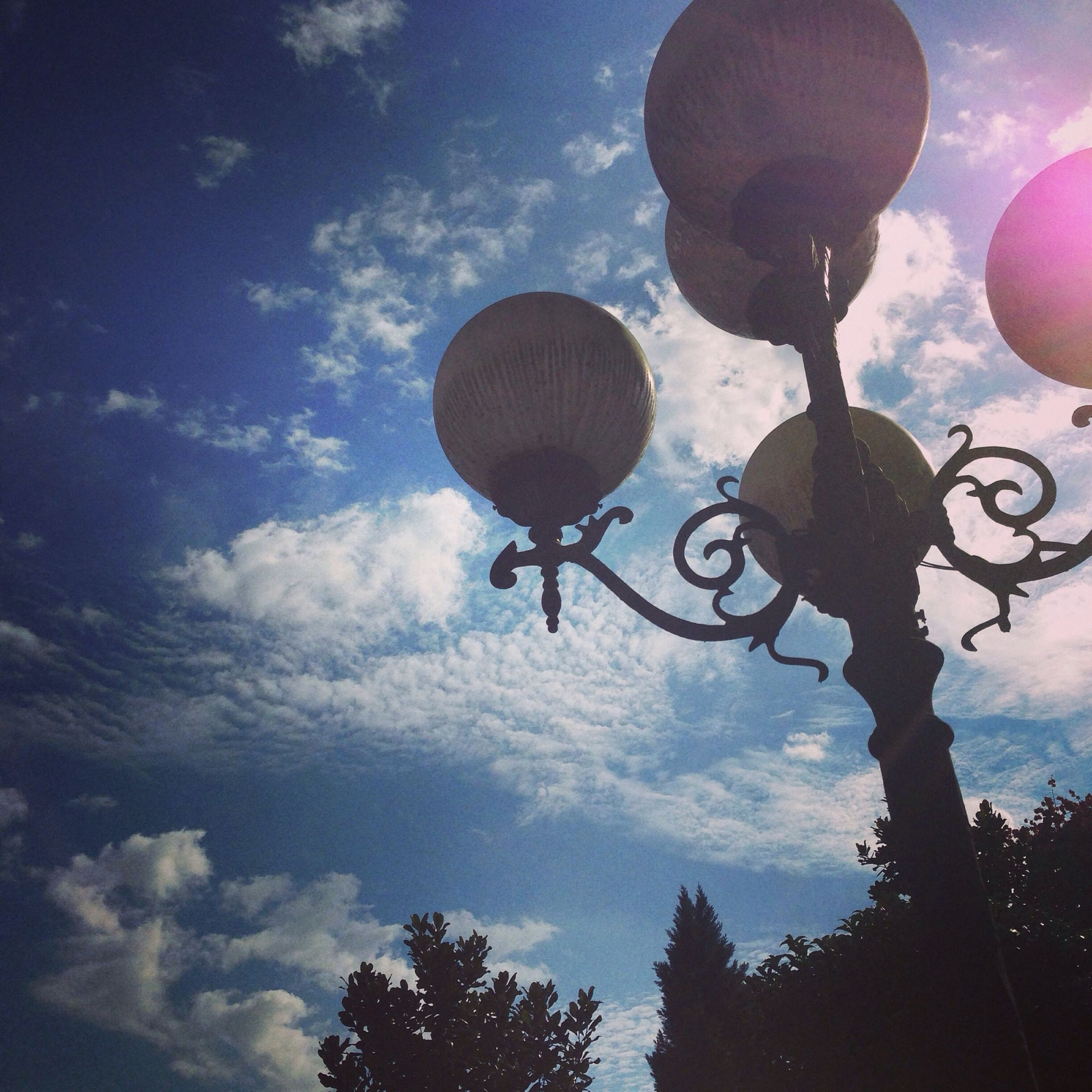 low angle view, sky, tree, lighting equipment, street light, hanging, cloud - sky, silhouette, balloon, outdoors, nature, cloud, blue, dusk, branch, day, leisure activity, electric light, sphere