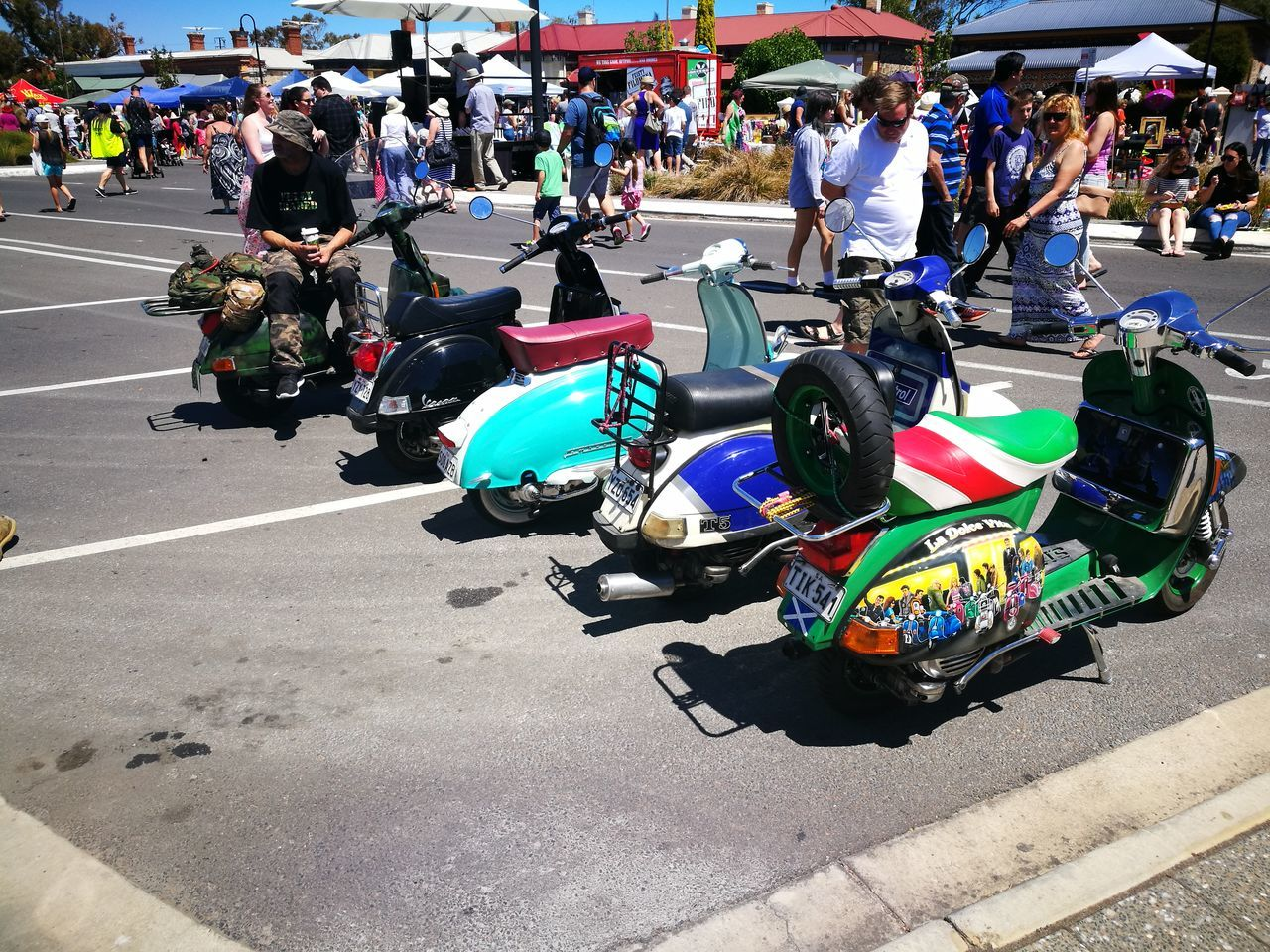 real people, large group of people, transportation, motorcycle, outdoors, day, street, land vehicle, men, women, sunlight, lifestyles, sitting, crowd, city, people