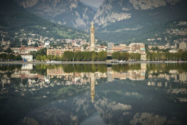 Scenic view of lake como by buildings and mountains