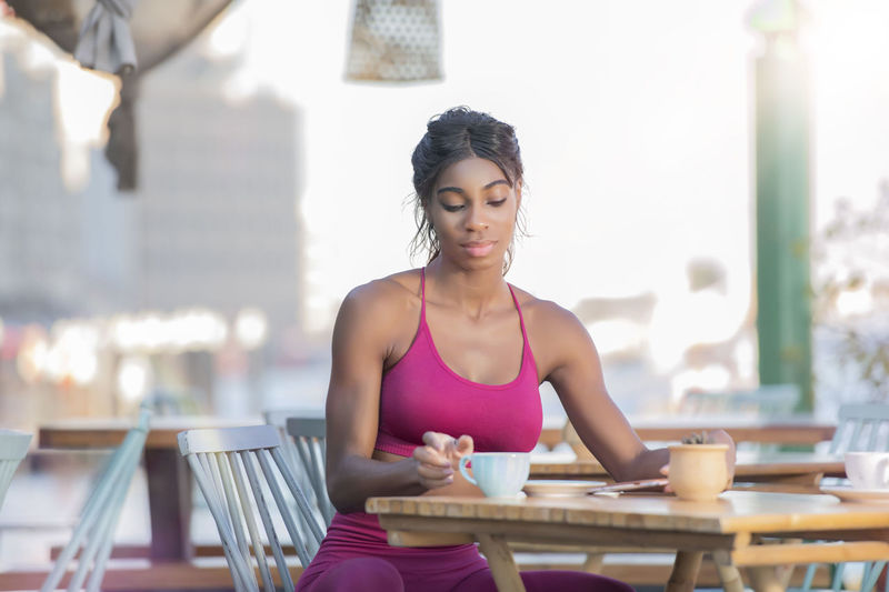 Young Woman Having Coffee Sitting At Table In Restaurant