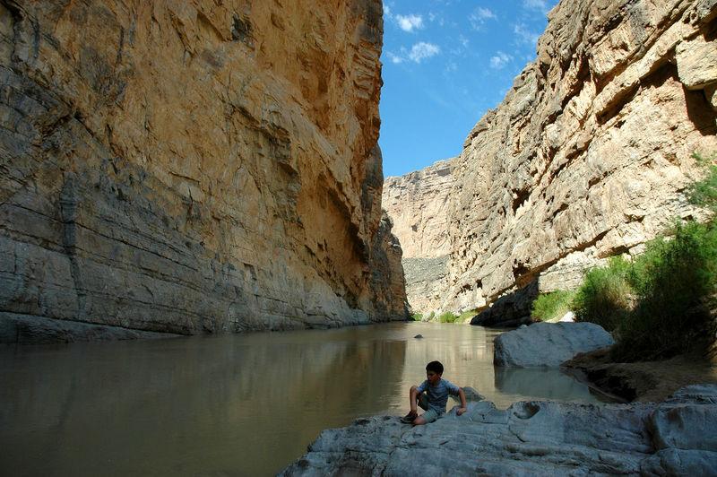 Boy sitting on rock at lakeshore