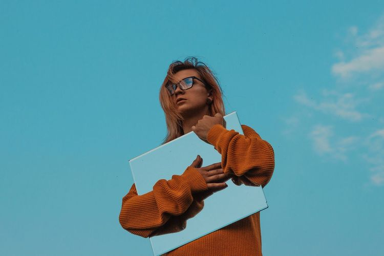 Low angle view of woman holding mirror against blue sky
