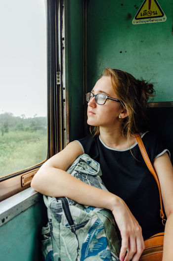 Young woman looking away while sitting on window
